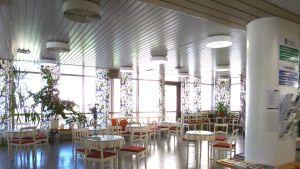 Mjölbolsta sjukhusingång med sina ljusa bord och stolar en solig vårdag.
