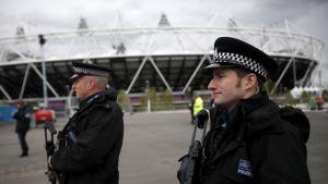 Två beväpnade poliser patrullerar utanför stadion i London innan OS 2012
