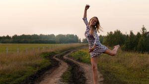 Flicka dansar på äng