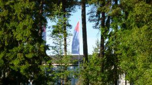 Lastbilstillverkaren Sisus fabrik och företagets flagga skymtar bakom träd.