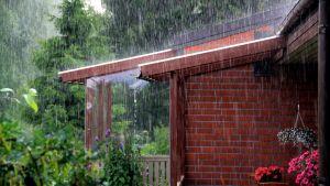 Häftig regnskur sköljer radhusterass.