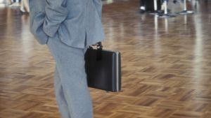 Kostumklädd affärsman som bär på portfölj