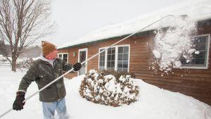 En man röjer snö vid sitt hus i Massachusetts