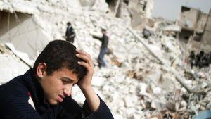 En syrisk tonåring i ruinerna efter en missilattack i Aleppo i Syrien