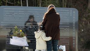 En sörjande mamma med sin dotter vid ett minnesplakat för de som omkom i katastrofen.