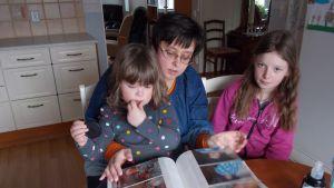 Camilla Palén tillsammans med döttrarna Sissel och Sandra tittar på bilder av sonen och brodern Hannes som dog endast fem år gammal.