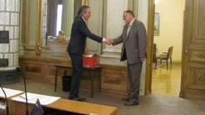 Revisionnämndenordförande Martti Wallasvaara skakar hand med stadsfullmäktiges ordförande Seppo Lehtinen.