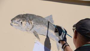 Heikki Kukkonen målar fisk