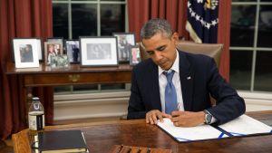President Obama undertecknar en lag som säkerställer löneutbetalningar till militären.