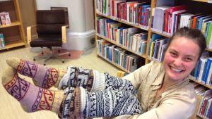 Emma Petrov med yllesockorna som någon i tidsbanken stickat henne.