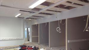 Byggarbetsplats inomhus, kontorsbygge, verktyg på golvet, elledningar hänger i taket.