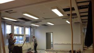 Kontorsbygge inomhus, två byggkarlar jobbar, verktyg på golvet.