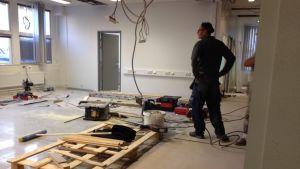 Verktyg och virke på golvet vid ett kontorsbygge.