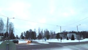 Några bilar i en korsning. Snö på vägen.