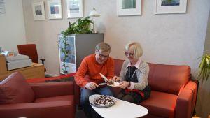 Dag Andersson, ordförande för Kulturföreningen Lande och Luckans verksamhetsledare Anne Lindroos provsitter nya soffan.