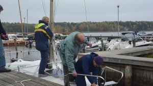Tre gubbar avlägsnar masten från en segelbåt i Ormnäs hamn Ekenäs