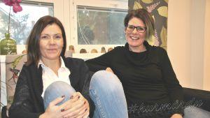 Eva Åstrand och Camilla Pitkänen sitter i en soffa.