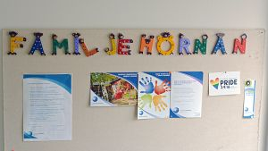 En anslagstavla där det står Familjehörnan med färgglada bokstäver. På tavlan finns olika informationspapper uppsatta.