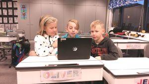 Emilia Eriksson, Oliver Helenius och Lasse Rantanen sitter vid en dator i Kirjala skola.