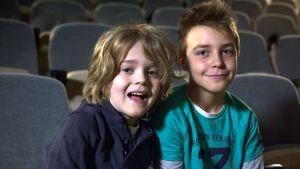 Rasmus och Kent från Degerö lågstadium sitter i en mörk sal på premiären för Det förlorade ägget.