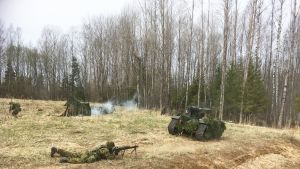 Estniska soldater förevisar ett scenario där en grupp soldater utrustade med fjärrstyrda obemannade bandfordon attackerar en mindre fiendepostering.