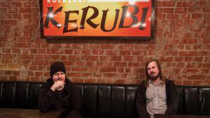 Muusikot Aki Tykki ja Ville Karttunen istuvat mustassa nahkasohvassa, yläpuolellaan valomainos jossa lukee Ravintola Kerubi.
