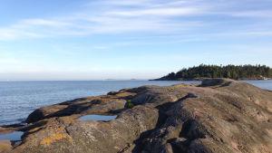 Rövargrundets klippor med utsikt över Rövaren, havet och horisonten. Esbo skärgård utanför sommaröarna.