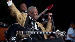 Bluessångaren B B King på scenen med gitarr i famnen