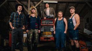 Fem fula män i en lada. En sitter på en Massey Ferguson traktor.