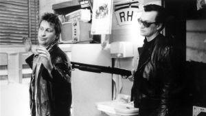 Taksikuski Alex (Kari Väänänen) uhattuna. Haulikkoa pitelee ohjaaja Wim Wenders elokuvassa Helsinki Napoli All Night Long.