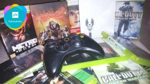 En hög med olika datorspel och en spelkonsol.