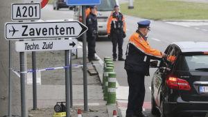 Poliser granskar en bil utanför Zaventem flygplats i Bryssel.