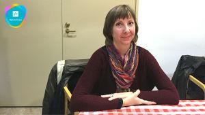 Nina som sitter vid ett bord.