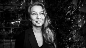 Pitkähiuksinen nainen, Soila Valkama, katsoo hymyillen kuvassa oikealle.
