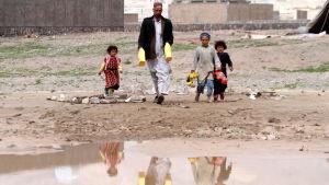 En afghansk far och tre barn går i lera vid en stor pöl i ett flyktingläger i Herat i Afghanistan.