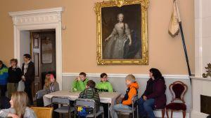 Skoleleverna får höra om Drottning Lovisa som syns på den stora tavlan.