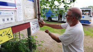 Uffe Johansson nitar fast bokbussens öppettider på Pellinge sommartorg.
