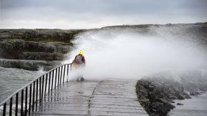Kvinna tar sig över vågbrytare vid Ugnsholmen i Helsingfors