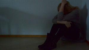 Nuori nainen istuu huoneen nurkassa ja nojaa poviinsa kyynärpäillään.