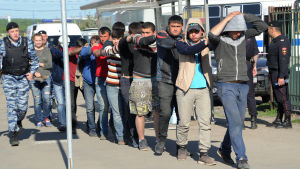 Ryska kravallpolis leder bort anhållna personer efter slagsmål.