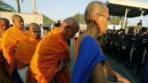 Minst ett par tusen poliser och soldater har omringat Wat Dammakaya-templet som skyddas av munkar och anhngare