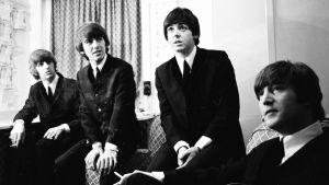 En pressbild på The Beatles klädda i kostymer.