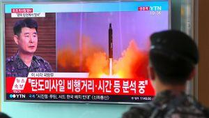 Sydkoreansk soldat följer med en tv-sändning om Nordkoreas senaste missiltest på en järnvägsstation i Seoul 4.7.2017.