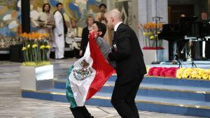 Ung man protesterar med mexikansk flagga vid Nobel fredsprisceremonin i Oslo