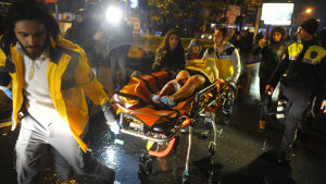 En skadad person förs till ambulans av vårdpersonal.