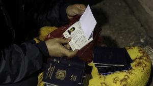 Den grekiska sjöbevakningen samlar in pass av syriska flyktingar på ön Kos