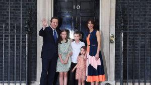 David Cameron tillsammans med sina tre barn och frun Samantha utanför premiärministerns bostad 10 Downing Street med en svart dörr med siffran 10 på.