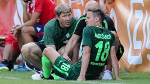 Niklas Moisander sitter på gräset och får behandling
