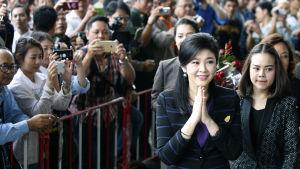Jingluck Shinawatra hälsar på sina anhängare då hon anländer till domstolen i Bangkok. Hon riskerar upp till tio års fängelse