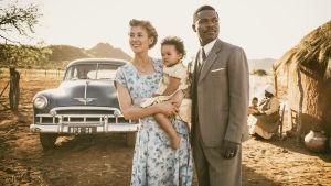Ruth (Rosamund Pike) håller i dottern och bredvid henne står maken Seretse (David Oyelowo).